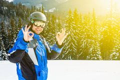 Young handsome man in winter sportswear looking away, wearing big mirrored ski mask. Man in blue ski suit looks at camera and smiles Royalty Free Stock Photo