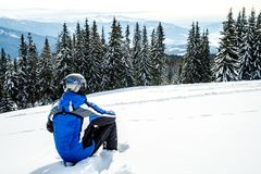 Young handsome man in winter sportswear looking away, wearing big mirrored ski mask. A man in a blue ski suit is sitting on the snow on top of a mountain Stock Photos