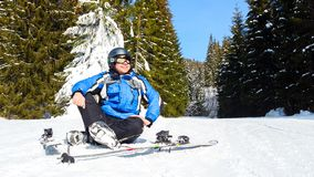 Young handsome man in winter sportswear looking away, wearing big mirrored ski mask. A man in a blue ski suit is sitting on the snow on top of a mountain Stock Image