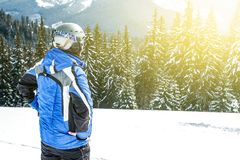 Young handsome man in winter sportswear looking away, wearing big mirrored ski mask.  Royalty Free Stock Photo