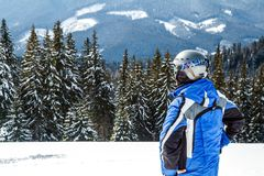 Young handsome man in winter sportswear looking away, wearing big mirrored ski mask.  Royalty Free Stock Photography