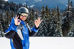 Young handsome man in winter sportswear looking away, wearing big mirrored ski mask. Man in blue ski suit looks at camera and smiles Stock Photos