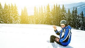 Young handsome man in winter sportswear looking away, wearing big mirrored ski mask. A man in a blue ski suit is sitting on the snow on top of a mountain Royalty Free Stock Images