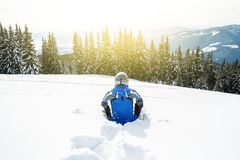 Young handsome man in winter sportswear looking away, wearing big mirrored ski mask. A man in a blue ski suit is sitting on the snow on top of a mountain Royalty Free Stock Image
