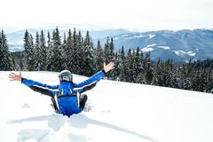 Young handsome man in winter sportswear looking away, wearing big mirrored ski mask. A man in a blue ski suit is sitting on the snow on top of a mountain Royalty Free Stock Photos