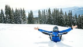 Young handsome man in winter sportswear looking away, wearing big mirrored ski mask. A man in a blue ski suit is sitting on the snow on top of a mountain Stock Images