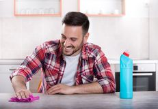 Man wiping kitchen table. Young handsome man wiping dining table with cloth and smiling. Kitchen in background. Husband doing housework Royalty Free Stock Photo