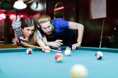 Young handsome man and woman flirting while playing snooker Stock Photography