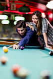 Young handsome man and woman flirting while playing snooker Royalty Free Stock Photography