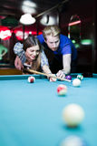 Young handsome man and woman flirting while playing snooker Stock Image