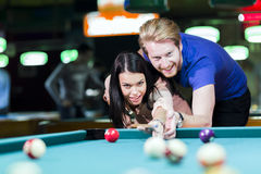 Young handsome man and woman flirting while playing snooker Stock Photos