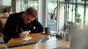 Young handsome man is working on blueprint, sitting at table in cozy cafe. Interior. Attractive young businessman is writing in notepad. Shot in slow motion stock footage