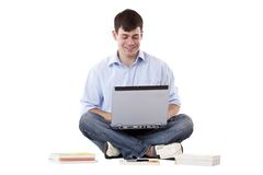 Young, handsome man working at floor on computer Royalty Free Stock Photos