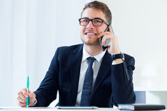 Young handsome man working in his office with mobile phone. Royalty Free Stock Image