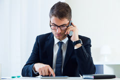 Young handsome man working in his office with mobile phone. Stock Photo