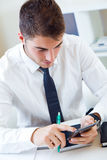 Young handsome man working in his office with mobile phone. Royalty Free Stock Photo