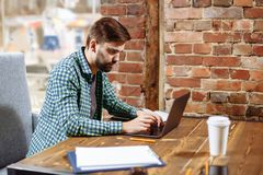 Young handsome man working with laptop in a cafe. royalty free stock photo