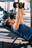 Young handsome man working out with dumbbells in a fitness gym.  Stock Photography