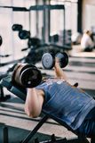 Young handsome man working out with dumbbells in a fitness gym.  Stock Images