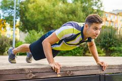 Man doing push ups outdoor. Young handsome man working out outdoor. Sporty guy flexing his muscles doing push ups royalty free stock images