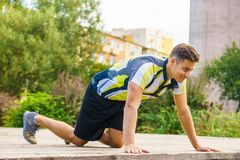 Man doing push ups outdoor. Young handsome man working out outdoor. Sporty guy flexing his muscles doing push ups stock photo