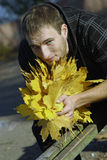 Young handsome man with yellow leaves Royalty Free Stock Photo