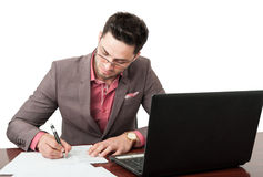 Young and handsome manager signing business documents. On his desk on his office with an open laptop near him Stock Photography