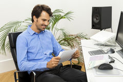 Young handsome manager sitting at his desk in the office Stock Images
