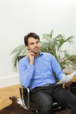Young handsome manager sitting at his desk in the office Royalty Free Stock Images