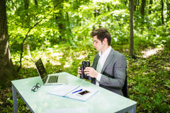 Young handsome manager at work table office with laptop in green forest with binocular looking for competitors. Business concept Royalty Free Stock Photography