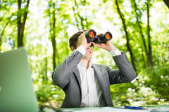 Young handsome manager at work table office with laptop in green forest with binocular looking for competitors. Business concept Royalty Free Stock Photos