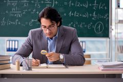 The young handsome math teacher in classroom. Young handsome math teacher in classroom stock photos
