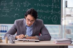 The young handsome math teacher in classroom. Young handsome math teacher in classroom royalty free stock photos