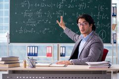 The young handsome math teacher in classroom. Young handsome math teacher in classroom royalty free stock images