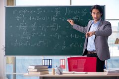 The young handsome math teacher in classroom. Young handsome math teacher in classroom stock image