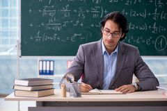 The young handsome math teacher in classroom. Young handsome math teacher in classroom royalty free stock photography