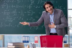 The young handsome math teacher in classroom. Young handsome math teacher in classroom stock images