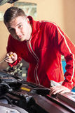 Young handsome mechanic checking the oil level in a car engine Royalty Free Stock Photos