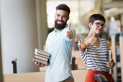 Young handsome men and attractive women are learning together and showing thumb up. Students are studying in library. Young handsome men and attractive women Stock Photography