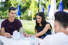 Men and women sitting at table drinking. Young handsome men and attractive women sitting at white plastic table drinking smoking talking and enjoying themselves Royalty Free Stock Photo