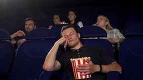Handsome man falling asleep during movie at the cinema stock photos