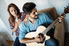 Young handsome man playing guitar while his girlfriend is singing Royalty Free Stock Photo
