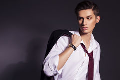 Young handsome men in suit shirt and red tie wear watches lookin Royalty Free Stock Images