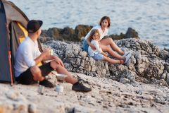 Man sitting on rocky coast looking at his wife and daughter,sitting near. stock image