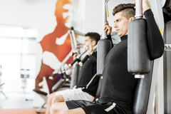 Young handsome men working out in a  gym. Two handsome men working out in a beautiful fitness center Stock Images