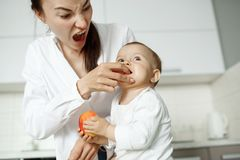 Young handsome mother feeding with peach her little son in kitchen. Mom making funny expression to make laugh her child. Young handsome mother feeding with Stock Photo