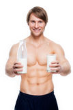 Young handsome muscular man holds milk. Royalty Free Stock Images