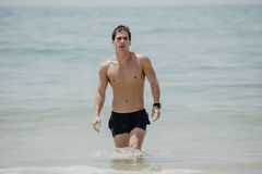 Young handsome muscular man walking out of the water in a tropical beach wearing a bathing suit royalty free stock photos