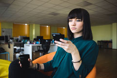 Young handsome office worker in a modern office in background jobs. Business woman holding a cup of coffee. Break work. Royalty Free Stock Images