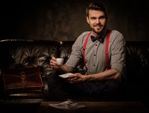 Young handsome old-fashioned bearded man with cup of coffee sitting on comfortable leather sofa on dark  background. Royalty Free Stock Photos